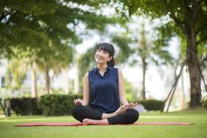bella donna yoga sul parco verde green foto