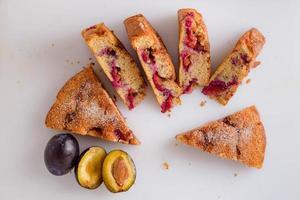 pasta di prugne tagliata a pezzi, deliziosa torta di prugne su una lavagna bianca con decorazione di prugne fresche. foto