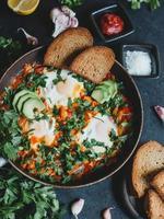shakshuka con uova, pomodori, peperone e prezzemolo in padella. shakshuka è un cibo tradizionale israeliano. foto