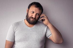 uomo barbuto in maglietta grigia che tiene il cellulare foto