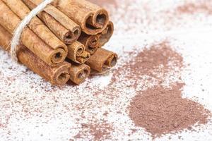 bastoncini di cannella e accessori di cacao in polvere per un'accogliente serata invernale vicino al camino con un bicchiere di vino foto