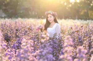 una donna che guarda i fiori in un campo di fiori con farfalle la sera, luce arancione. foto