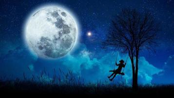 immaginazione le ragazze stanno cullando in mezzo a molte stelle e luna piena di notte. foto