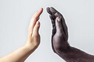 mani maschili nere e femmine bianche, palmi aperti l'uno verso l'altro. un simbolo della lotta per i diritti dei neri in America. il concetto di uguaglianza e la lotta al razzismo foto