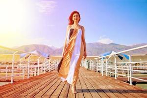 ragazza dai capelli rossi in posa in un abito svolazzante sul molo. foto