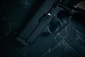 pistola sul tavolo texture cemento verde. foto
