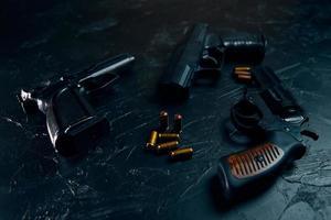 tre pistole e proiettili sul tavolo nero. foto