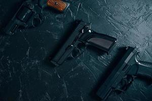 tre pistole sul tavolo nero. foto