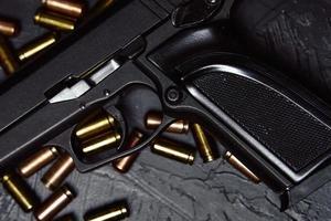 pistola nera e proiettili sul tavolo. foto