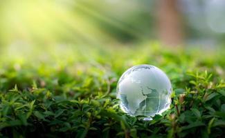 concetto salva il mondo salva ambiente il mondo è nell'erba dello sfondo verde bokeh foto