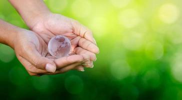 concetto salva il mondo salva l'ambiente il mondo è nelle mani dello sfondo verde bokeh foto