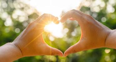 le mani delle donne e degli uomini sono a forma di cuore con la luce del sole che passa attraverso le mani foto