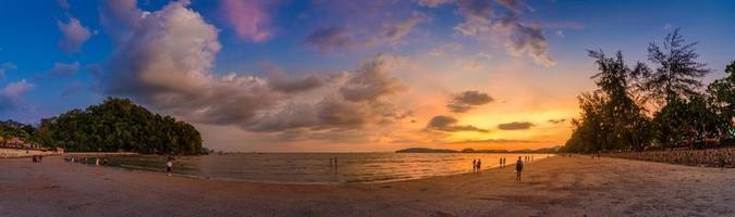 ao nang krabi thailandia la spiaggia è piena di gente la sera. foto panoramica a luce dorata