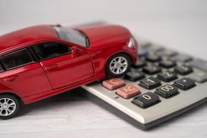 auto su calcolatrice, prestito auto, finanza, risparmio di denaro, assicurazioni e concetti di tempo di leasing. foto