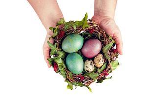 uova di Pasqua con decorazioni. uova di quaglia in un nido di uccelli tenere per mano di donna. foto