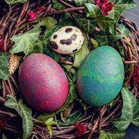 uova di Pasqua con decorazione.quaglia e uova di gallina in un nido di uccelli. foto