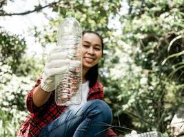 primo piano di volontari seduti e raccogliere immondizia nel parco. inquinamento da plastica ambientale. il concetto di giornata mondiale dell'ambiente. zero rifiuti. foto