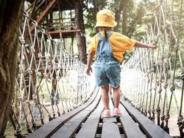 la vista posteriore della ragazza stava camminando su un ponte di legno sospeso con reti o corrimano in corda nel parco giochi. foto