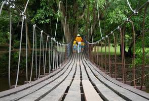 vista posteriore della famiglia che cammina sul ponte sospeso in legno con reti o corrimano in corda nel parco. foto
