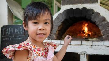una bambina fa la pizza fatta a mano e sta sorridente davanti a un forno per pizza in mattoni di legno in un cortile all'aperto in un ristorante. foto