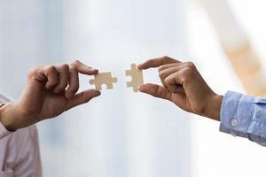mani di uomini d'affari che collegano puzzle. concetto di lavoro di squadra di affari. foto