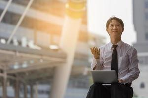 uomo d'affari asiatico seduto sul marciapiede e lavorando con il taccuino foto