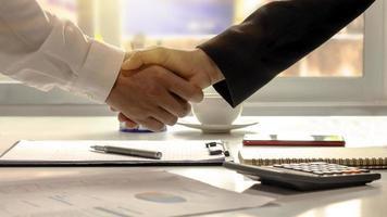 gli uomini d'affari hanno terminato l'incontro e la felice stretta di mano dell'uomo d'affari dopo che il contratto è stato stipulato per essere un partner di lavoro di squadra insieme. foto