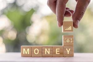 una mano che tiene un blocco di legno quadrato con icone grafiche con messaggi di denaro. idee per la crescita finanziaria e aziendale. foto