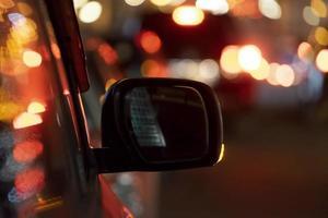 specchietto per auto sullo sfondo della notte foto