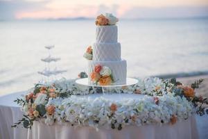 torta nuziale al matrimonio sulla spiaggia al tramonto foto