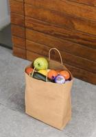 borsa del cibo consegnata dalla porta della persona foto