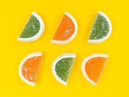 fette di agrumi marmellata di arancia e verde in zucchero su sfondo giallo. foto