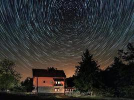 tracce stellari sopra la casa. edificio residenziale e le tracce delle stelle nel cielo. il cielo notturno è astronomicamente preciso. foto