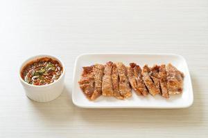 collo di maiale alla griglia o collo di maiale bollito al carbone con salsa piccante tailandese foto