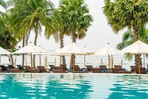 sedia a sdraio vuota con ombrellone intorno alla piscina foto