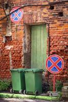 due bidoni della spazzatura in piedi sulla strada con un muro di mattoni rossi con una porta di legno verde e due segnali stradali restrittivi foto