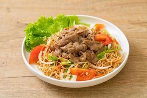 Insalata piccante di noodle istantanei con carne di maiale su un piatto bianco - stile cibo asiatico foto