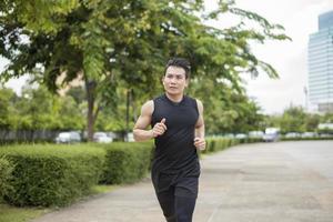 bell'uomo sportivo che corre in una città all'aperto foto