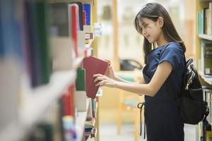 studentessa universitaria asiatica di belle donne in biblioteca foto