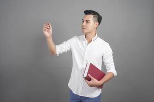 ritratto di uomo studente universitario con libro in studio sfondo grigio gray foto