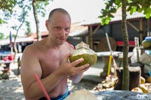 Uomo caucasico che beve dalla noce di cocco a Echo Beach a Bali foto
