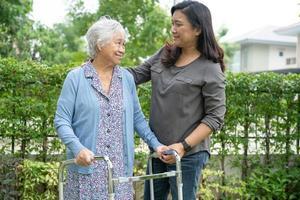 aiutare e curare la donna anziana o anziana asiatica anziana usa il camminatore con una buona salute mentre cammina al parco in una felice vacanza fresca. foto