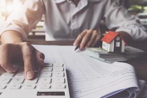 il cliente usa penne e calcolatrice per calcolare i prestiti per l'acquisto della casa foto