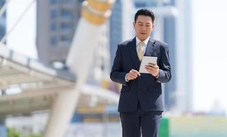 ritratto di uomo d'affari sorridente che guarda tablet foto