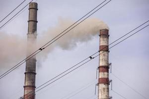 fumo da due camini industriali, tubi, contro il cielo. il riscaldamento globale. inquinamento dell'aria. inquinamento ecologico. emissioni atmosferiche che inquinano la città. i rifiuti industriali sono pericolosi per la salute. foto