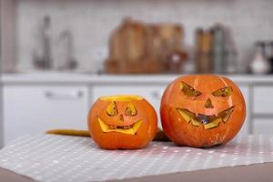 le zucche di halloween sorridono e gli occhi spaventosi per la notte di festa. vista ravvicinata di spaventose zucche di halloween con gli occhi sul tavolo a casa. messa a fuoco selettiva foto