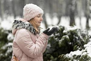 donna felice in una giornata invernale di neve nel parco, vestita con abiti caldi, soffia via la neve dai guanti foto