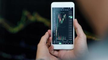 uomo d'affari trader investitore analista che utilizza l'analisi dell'app del telefono cellulare per l'analisi del mercato finanziario delle criptovalute, il grafico dell'indice dei dati di trading sullo smartphone foto