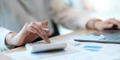 primo piano donna d'affari che utilizza calcolatrice e laptop per fare finanza matematica sulla scrivania di legno in ufficio e sfondo di lavoro aziendale, tasse, contabilità, statistiche e concetto di ricerca analitica foto