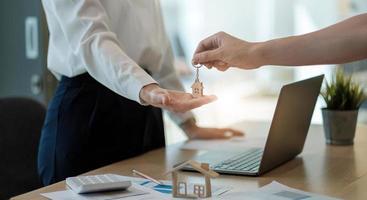 agente immobiliare che tiene la chiave di casa al suo cliente dopo aver firmato un contratto in ufficio, concetto di immobile, trasloco o affitto di proprietà foto